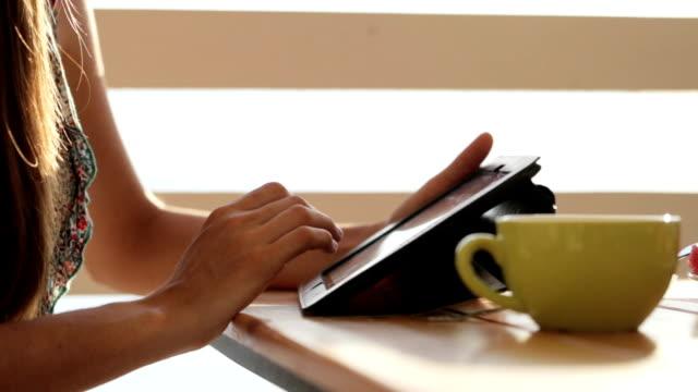 オープンエアのカフェでタブレットを使用してクローズ アップ女性の手。 ビデオ