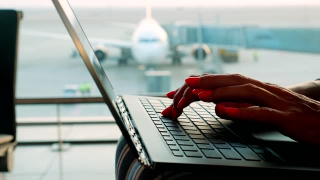 close-up, female hands, with bright red nails, are typing on a laptop in front of panoramic window, with runway and big plane view, at airport video