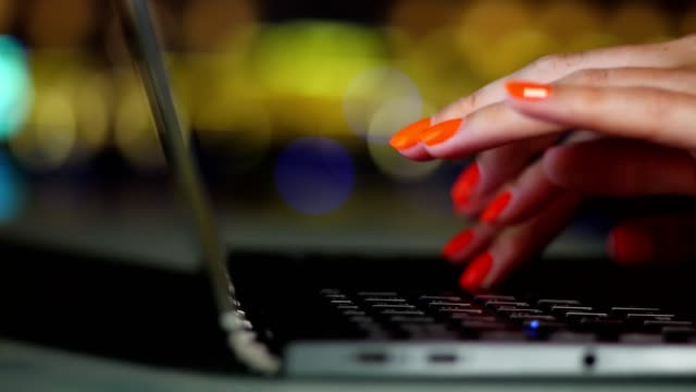 close-up, female hands with bright red nails, are typing on a laptop keyboard, on blurred city night lights background