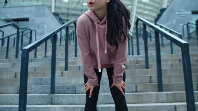 vidéos et rushes de pieds féminins de plan rapproché courant en bas des escaliers. fille fatiguée essuyant la sueur sur la rue de ville - joggeuse