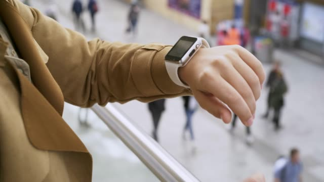 Close-up female looking at smartwatch on modern railway station Young woman standing on train station using modern clock. Close-up view female hand with smartwatch on wrist, she looking at display and waiting our train at blurred background with walking people railroad station platform stock videos & royalty-free footage