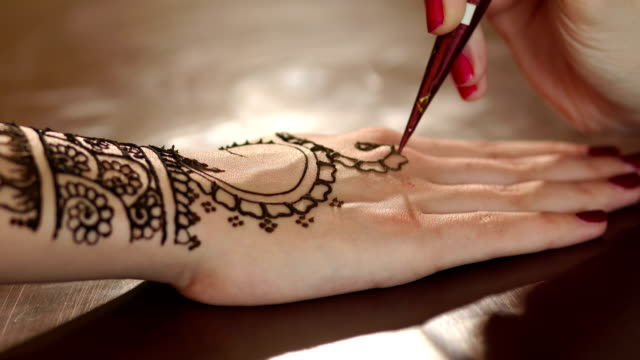 Close-up female's hands paint mehendi on hand. video