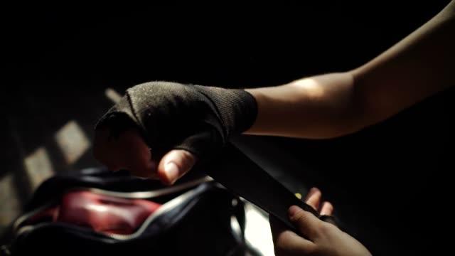 vídeos de stock, filmes e b-roll de closeup cabe as mãos de envolvimento de mulher com fita de bandagem, preparando-se para treinamento de boxe lenta - autodefesa
