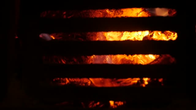 close-up flame tongues spreading around burned logs slow-mo - emettere video stock e b–roll
