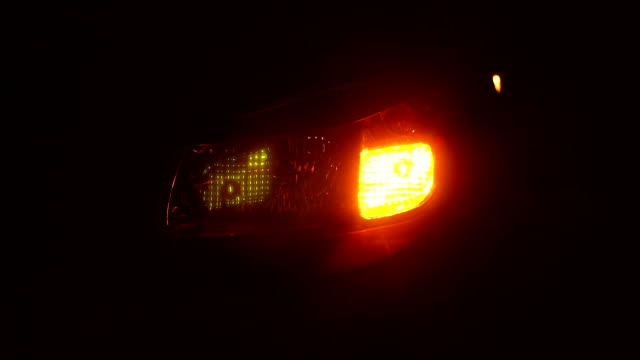Close-up flashing yellow rear light on the car at night. Slow motion.