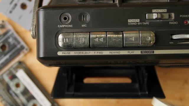 closeup fo man's hand inserting the audio cassette into the retro tape player. - mangianastri video stock e b–roll