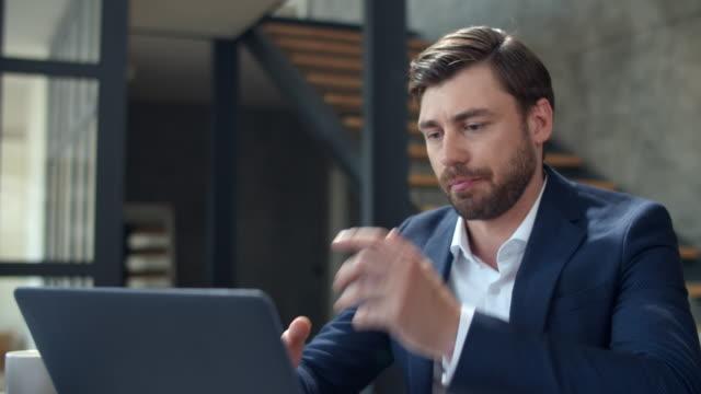 遠隔地のオフィスでラップトップカメラで話しているビジネスマンをクローズアップ。 - 人里離れた点の映像素材/bロール
