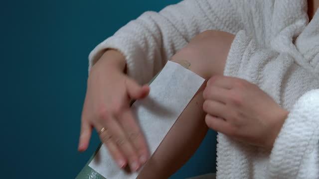 nahaufnahme fuß der jungen frau mit wachs epilation zu hause auf türkisen hintergrund. wachswärmer für die haarentfernung im körper - wachs epilation stock-videos und b-roll-filmmaterial