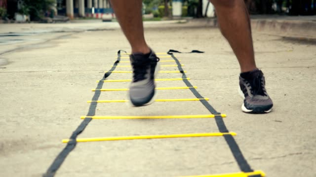 Close-up foot sportsman training with agility ladder equipment. Close-up foot sportsman training with agility ladder equipment. athlete exercise training outdoors in the public park concept. sportsperson stock videos & royalty-free footage
