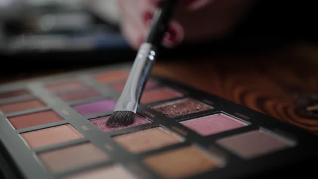 影とアーティストのパレットから色を使用してメイクのクローズ アップ映像。スローモーション - 舞台化粧点の映像素材/bロール