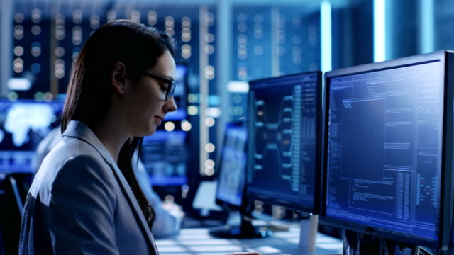 Close-up Footage of Female IT Engineer Working in Monitoring Room. She Works with Multiple Displays. In The Background Her Colleague Sitting at His Workstation. video
