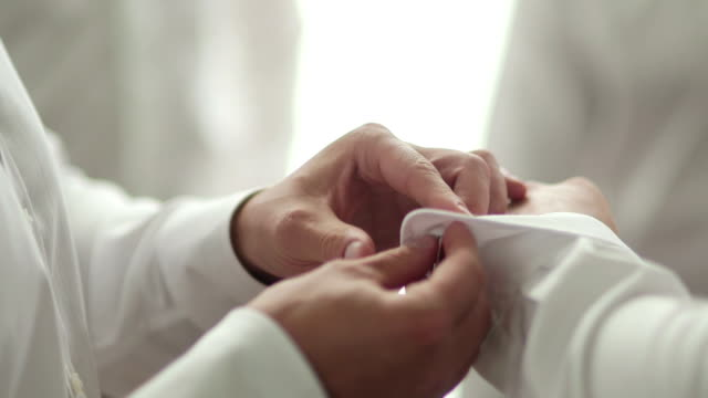 Close-up footage of male hands dressing groom. Man is adjusting cufflinks. video