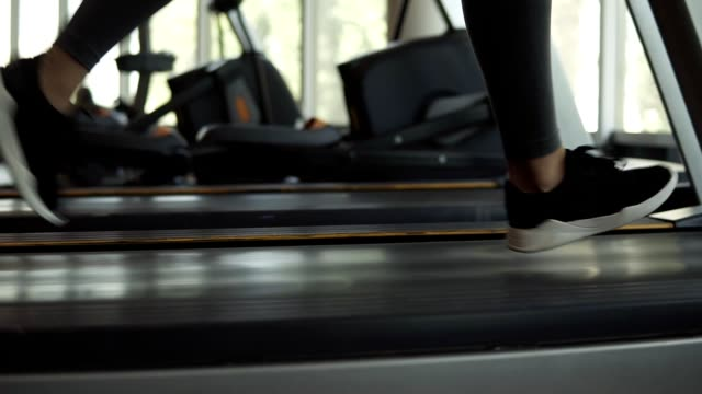 Closeup footage of woman's feet in snakers running on a treadmill in fitness club. Blonde woman in grey leggings and sport bra working out at gym