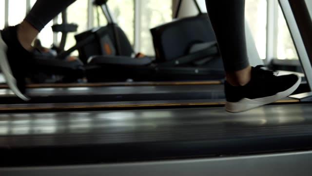 Closeup Aufnahmen von Frau die Füße in Snakers laufen auf einem Laufband im Fitness-Club. Blonde Frau im grauen Leggings und trainieren Sie im Fitness-Studio Sport-BH – Video