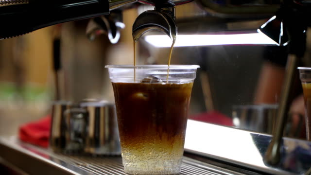 vídeos de stock e filmes b-roll de close-up fresh iced coffee, cold coffee with ice in disposable transparent cup simply pouring over ice. italian espresso machine. coffee culture and professional coffee making, coffe to go, service, catering concepts - café gelado