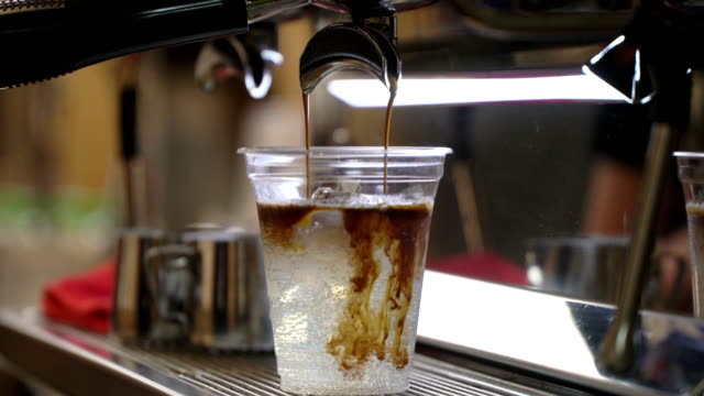 vídeos de stock e filmes b-roll de close-up fresh iced coffee, cold coffee with ice in disposable transparent cup simply pouring over ice. italian espresso machine. coffee culture and professional coffee making, coffe to go, service, catering concepts. timelapse - café gelado