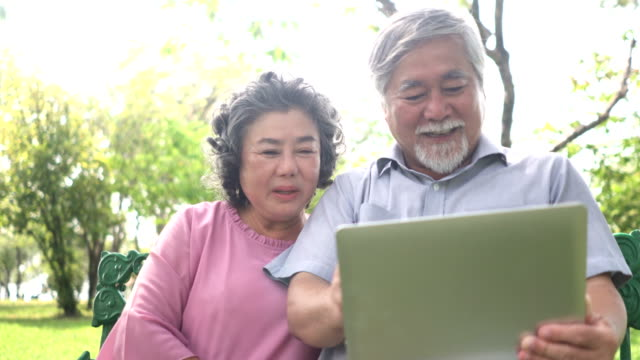 close-up front view : Senior Asian couple face time with their chlidren to show his love video