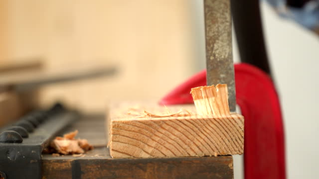 close-up front view: senior carpenter's hand carving on wood in the workshop house