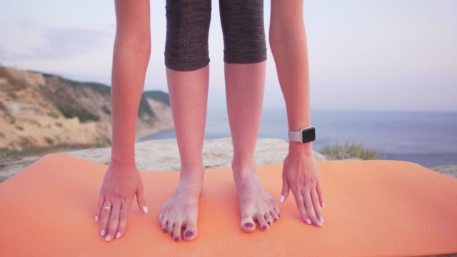 Close-up girl legs - stretching outdoors, morning or evening. Sports girl with a smart watch