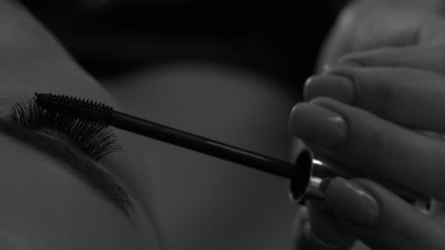 Close-up girl paints eyelashes with mascara on one eye. Make up. Close-up girl paints eyelashes with mascara on one eye. Make up. 4K 30fps ProRes 4444 mascara stock videos & royalty-free footage