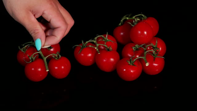 Close-up girl puts cherry tomatoes on a black mirror background. Slow motion.
