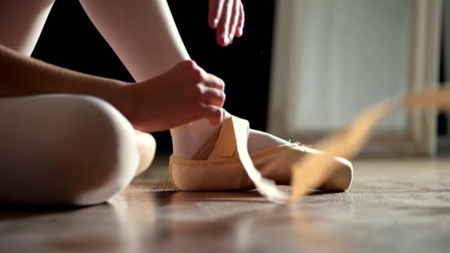 close-up. girl puts on pointe shoes, tied ribbons on pointe shoes, for practicing ballet , sitting on floor in the hall. ballet lessons , classical ballet dance school - vídeo