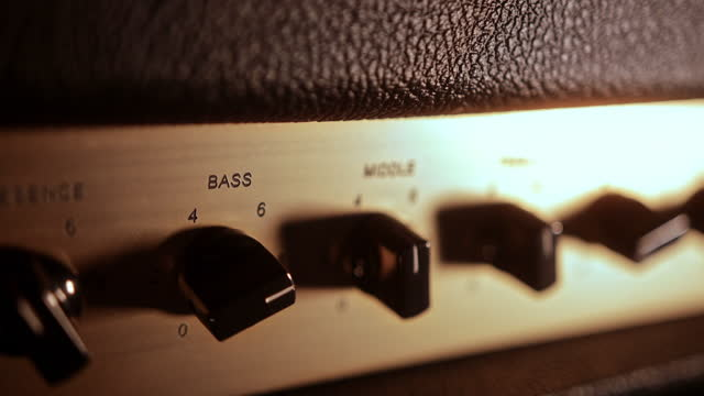 Close-up gold and black fader buttons of music amplifier