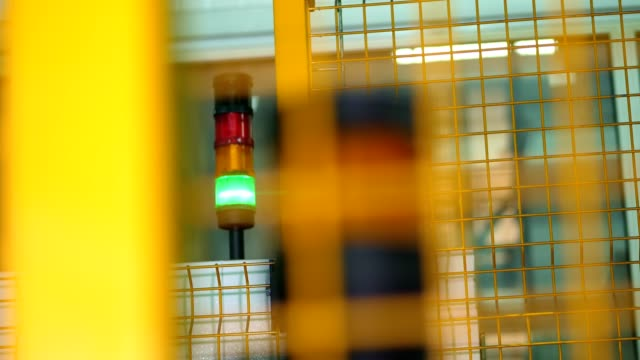 Closeup, Green and red electric bulbs in factory . warning sign, equipment behind the fence in factory