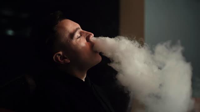 närbild kille med den fashionabla frisyr röka en vatten pipa i slow motion. - water pipes bildbanksvideor och videomaterial från bakom kulisserna