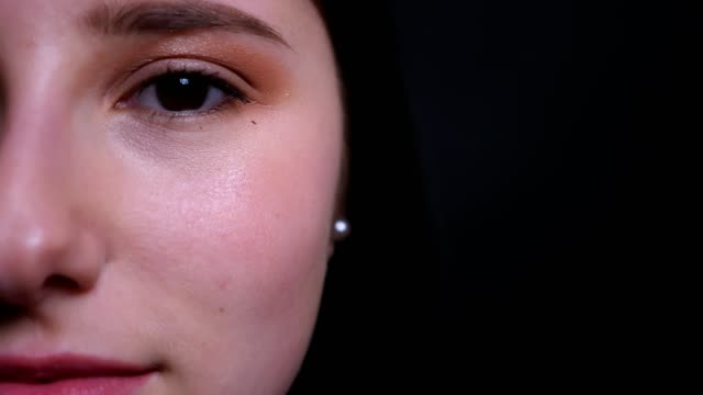 vídeos y material grabado en eventos de stock de primer plano media cara retrato de joven atractiva morena mujer con maquillaje bonito mirando directamente a la cámara con fondo aislado en negro - ojo morado