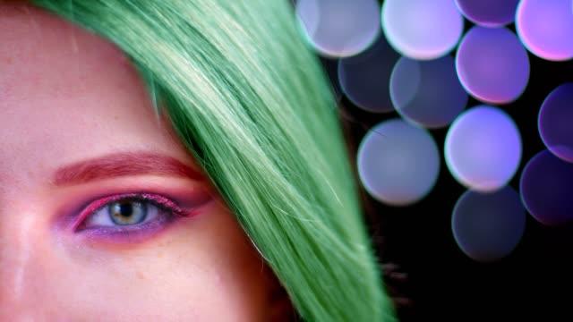 stockvideo's en b-roll-footage met close-up half gezicht schieten van jonge aantrekkelijke kaukasische vrouw met roze mooie roze glitter make-up met groen geverfd haar te kijken naar camera met bokeh achtergrond - portait background