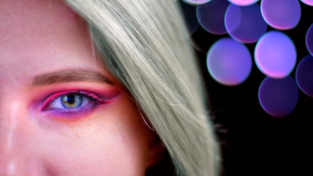 Closeup half face shoot of young attractive caucasian female with pink beautiful pink glitter makeup with mint dyed hair looking at camera with bokeh background Closeup half face shoot of young attractive caucasian female with pink beautiful pink glitter makeup with mint dyed hair looking at camera with bokeh background. blue hair stock videos & royalty-free footage