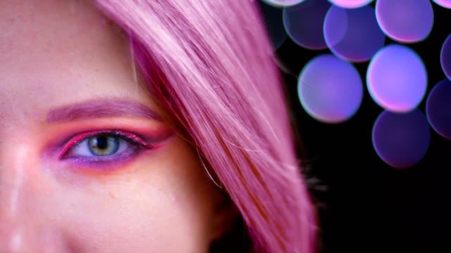 stockvideo's en b-roll-footage met close-up half gezicht shoot van jonge aantrekkelijke kaukasische vrouw met roze mooie roze glitter make-up met roze haar te kijken naar camera met bokeh achtergrond - roze haar