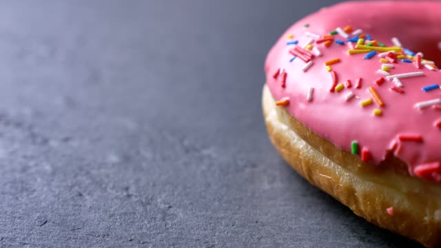 close-up half-shot of delicious pink donut with multicolored chips and eyes spinning slowly on gray table background. - bombolone video stock e b–roll
