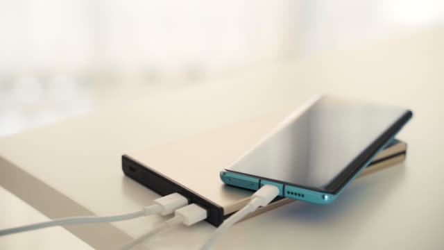 Closeup Hand Charging Adaptor to Mobile Smart Phone into Power Bank.