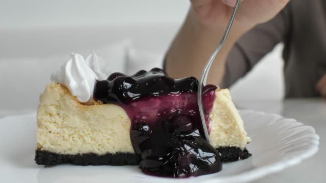 close-up hand cutting blueberry cheesecake - sernik filmów i materiałów b-roll