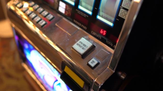 POV closeup hand hits button to start gambling on slot machine in casino video