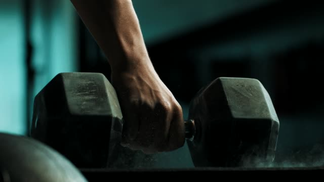 Close-up hand holding dumbbell Close-up hand holding dumbbell on the gym floor. cross training stock videos & royalty-free footage