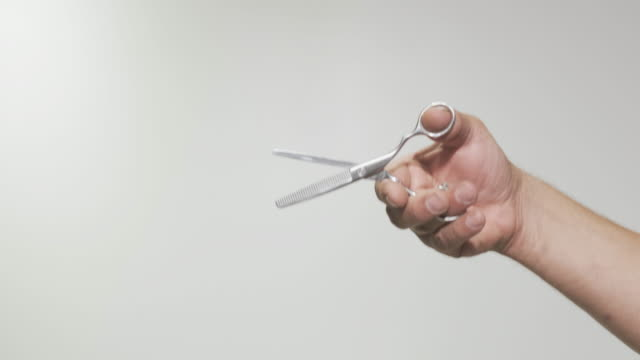 close-up hand of a man hairdresser holding thinning scissors - forbici video stock e b–roll