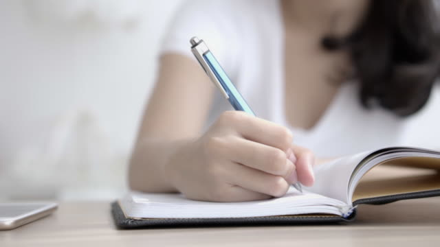 Closeup hand of asian woman sitting in the living room study and learning writing notebook and diary on table at home, girl homework, businesswoman planning working on table, education concept.