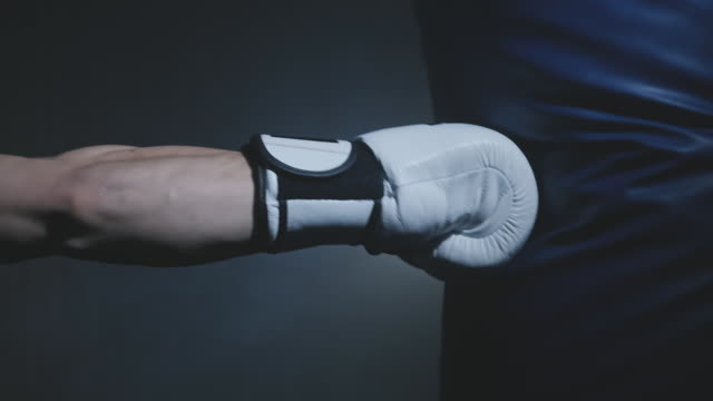 close-up hand of boxer punching bag in white gloves over dark background. - sacco per il pugilato video stock e b–roll