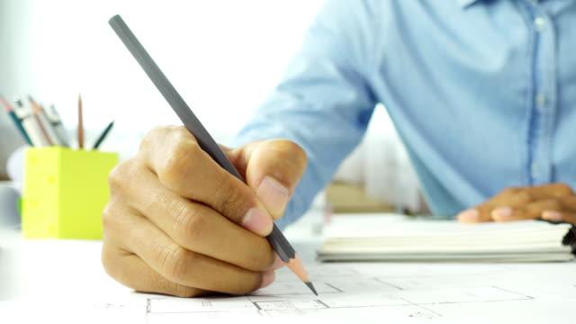 Close-up main de l'homme de confiance architecte en vêtements de travail sur le bureau. Concept de construction travaillant sur le projet de la maison. - Vidéo