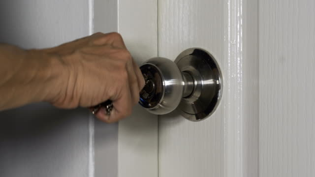 closeup hand of someone is using key open the door - serratura video stock e b–roll