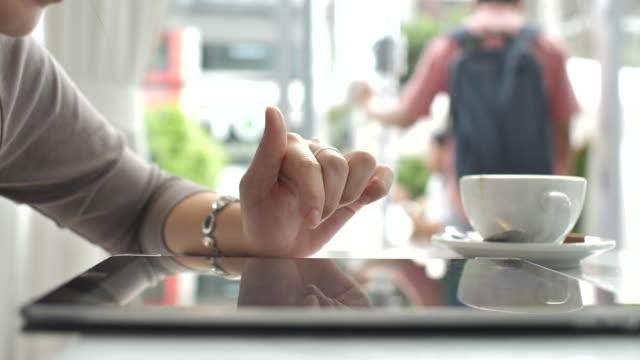 stockvideo's en b-roll-footage met close-up hand van vrouw hand met digitale tablet in koffie café - een tablet gebruiken