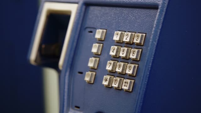 Closeup Hand of Woman Using Public Telephone or Phone Booth Station.