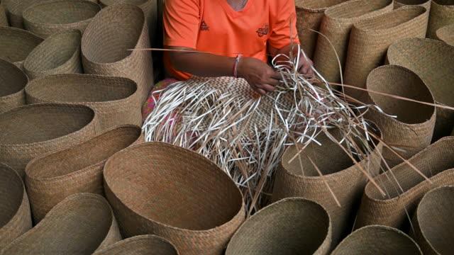 närbild hand av kvinnan vävning en torr ledighet för vävning göra korg, hand hantverk produktion av korg - väva bildbanksvideor och videomaterial från bakom kulisserna