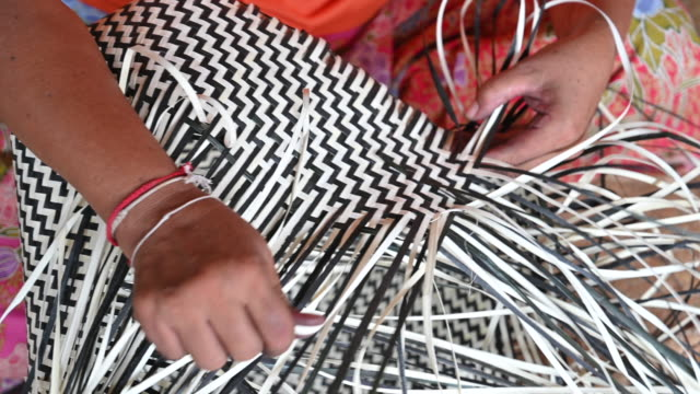 close-up hand of  woman weaving a dry leave for weaving making basket, hand craft production of basket - тростник стоковые видео и кадры b-roll
