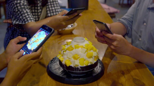Closeup Hand of Young Asian Man and Woman Take Candid Photo of Mango Kakigori Cheese Cake or Ichiko Kokigori a Famous Dessert in Korea and Japan and Thailand for Social Media Before Eat.