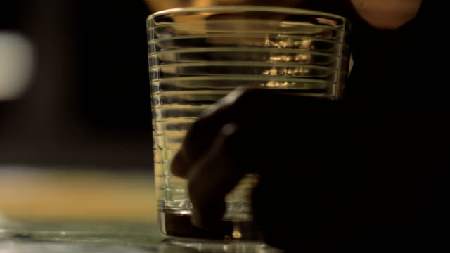 Closeup hand pouring alcohol from bottle in glass, drinking and putting on table video