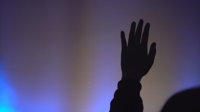 close-up hand raised at worship, silhouette shot - христианство стоковые видео и кадры b-roll